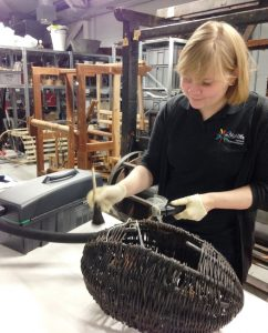 Rachael cleaning a wool basket, or mudag, in the store