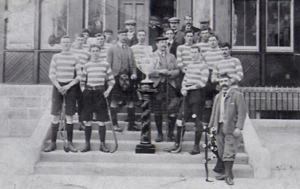 Newtonmore with their first Camanachd Cup win in 1907 on the steps of the Duke of Gordon Hotel, Kingussie. Johnnie Cattanach is second from the right on the third step back. Image credit: High Life Highland, Highland Folk Museum
