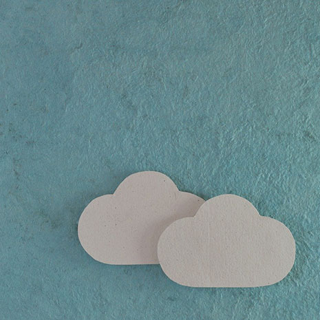 cutout paper clouds on blue card background.